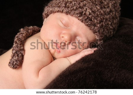 Newborn baby boy wearing a knitted hat. - stock photo