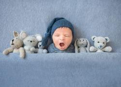 Newborn baby boy yawning and lying between plush toys