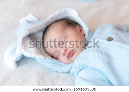 Newborn baby close-up. Side view of a newborn baby sleeping soundly on his back in a blue blouse with a hood and ears on a white background. Portrait of a sleeping newborn baby on a beige background.