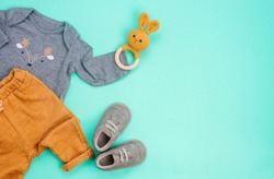 Newborn baby clothing and rabbit beanbag on turquoise background with blank space for text. Top view, flat lay.