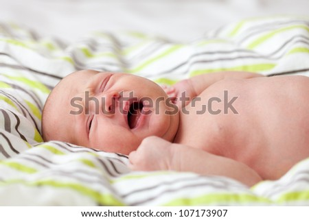 Newborn baby cryingg on the bed, selective focus