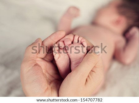 newborn baby feet in parents hands