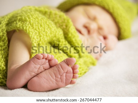 Newborn Baby Feet, New Born Child Sleeping, Kid Foot Covered by Green Knitted Wool Cloth