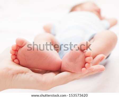 Newborn baby feet on female hand