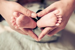 newborn baby feet on female hands