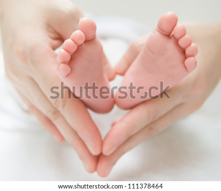 newborn baby feet on female hands, shape like a lovely heart