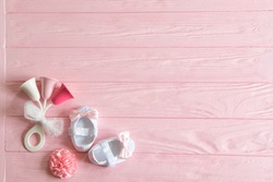 Newborn baby girl background. Newborn accessories for a baby girl on a pink wooden background.