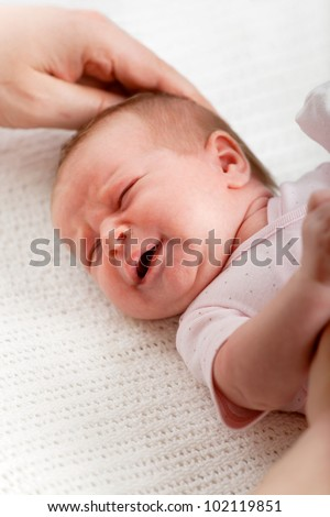 Newborn baby girl crying while her dad tries to comfort her, closeup shot