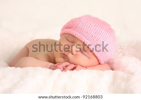 Newborn baby girl in a knitted pink hat.