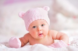 newborn baby girl in pink knitted bear hat and mittens on a bed