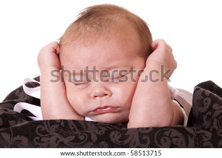 Newborn baby girl is sleeping  with her hands holding head up.