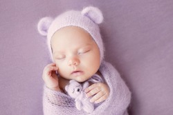 Newborn baby girl on a gray background in a hat with ears. A sweet newborn baby is sleeping. The first photo session of the baby.