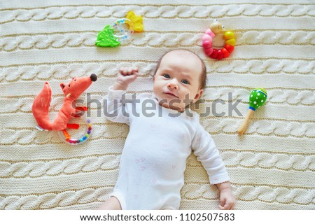 Newborn baby girl playing with colorful rattle toys. Development games for infants