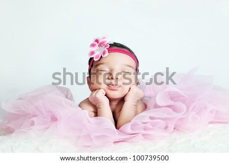 Newborn baby girl posing in tutu skirt and flower head band