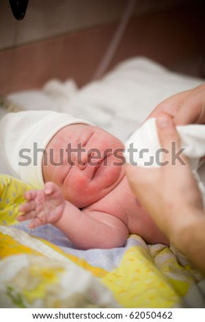 Newborn baby girl right after delivery, shallow focus