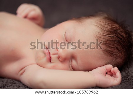 Newborn baby girl right after delivery. Sweet baby girl portrait. Shallow focus.