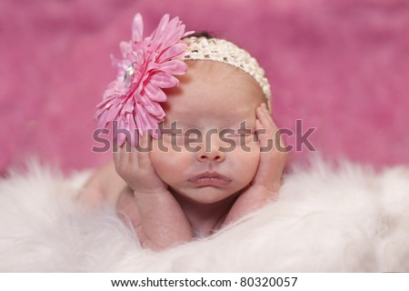 Newborn baby girl sleeping in a adorable position. Bright pink background and flower in hair.