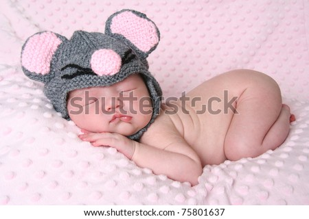 Newborn baby girl sleeping wearing a mouse hat.