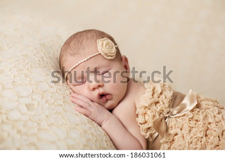 newborn baby girl wearing a  flower headband curled up and asleep on a textured blanket.