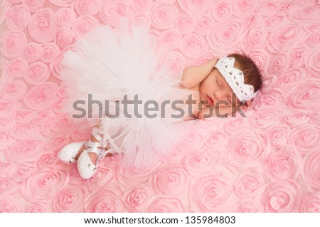 Newborn baby girl wearing a white crocheted crown, ballerina tutu, and ballet slippers. She is sleeping on pink rose ribbon fabric.