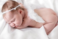 Newborn baby girl with angel wings.