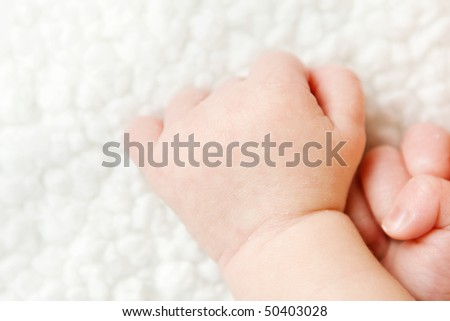 newborn baby hands on a blanket with copy space