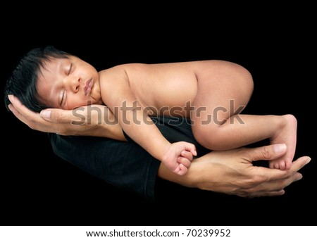 Newborn baby head resting in mother's hand, on black background, sleeping