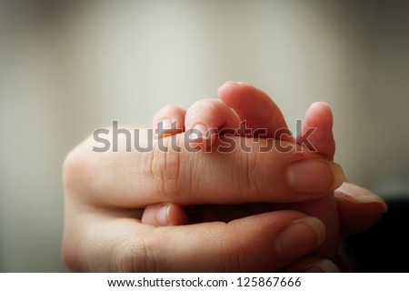 Newborn baby holding his mothers finger, selective focus