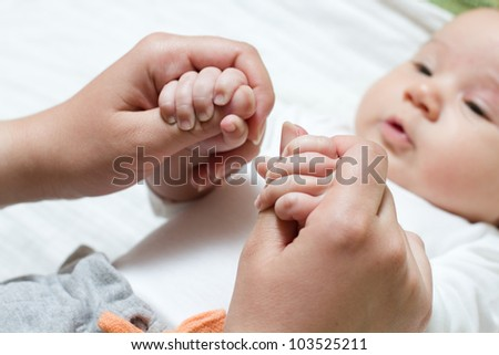 Newborn baby holding mother hand.