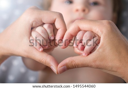 Newborn baby holding mother hands in heart shape , closeup baby's hand in mother's finger