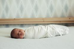 Newborn baby in a diaper sleeps on the bed. Childhood, infancy, parenthood, motherhood concept