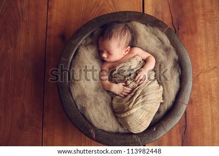 Newborn baby in a round wood bowl