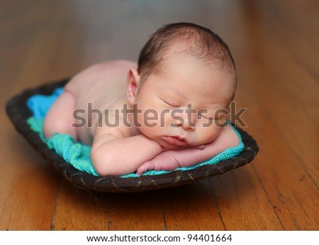 Newborn baby in a wood bowl, mix race: Caucasian and Asian