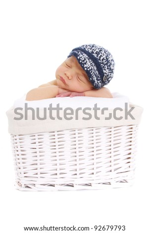 Newborn baby in blue hat sleeping in a basket on white background