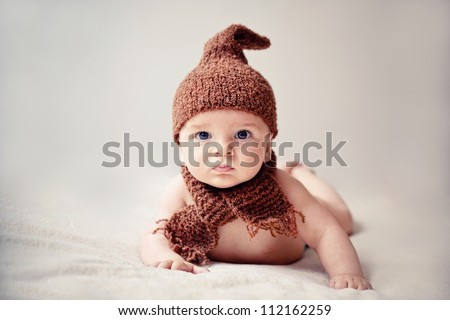 newborn baby in cap and scarf looking into the camera