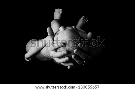 Newborn baby in fathers hands, black and white