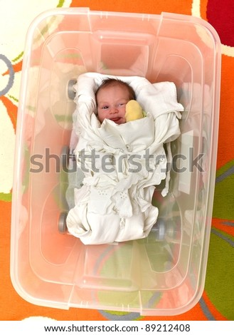 Newborn baby in open plastic box