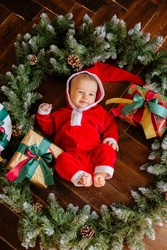Newborn baby in Santa Claus costume lies in the middle of a wreath of Christmas trees
