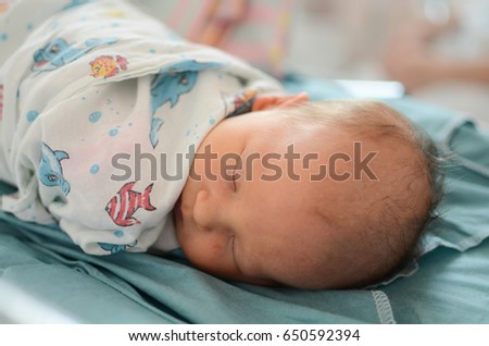 newborn baby in the delivery room the first hours of life swaddling Stock photo ©