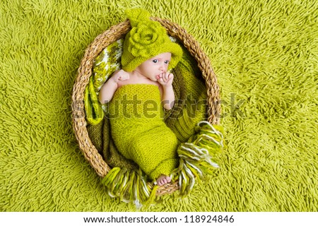 Newborn baby in woolen hat inside basket over green background