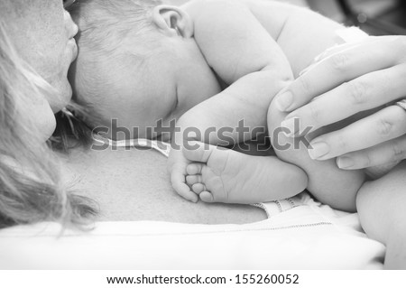 Newborn baby is holding his foot while asleep on mother's chest