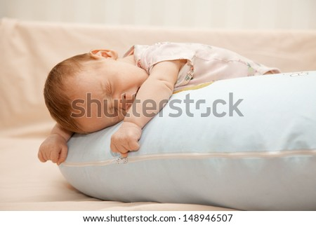 Newborn baby laying on the pillow on his tummy and yawning