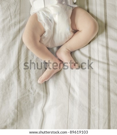 newborn baby legs and body on bed