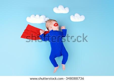 Newborn baby. Little super hero flying through the sky.