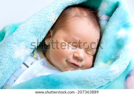 Newborn baby lying in a warm baby blanket and smiles