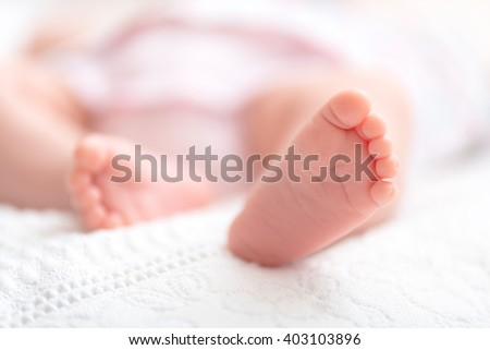 Newborn baby on a white blanket -  tiny baby feet closeup