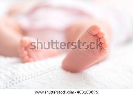 Newborn baby on a white blanket -  tiny baby feet closeup