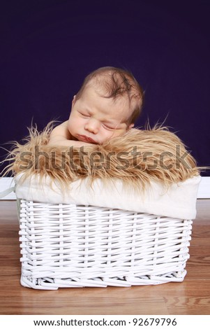 Newborn baby on fur in a basket, studio setting
