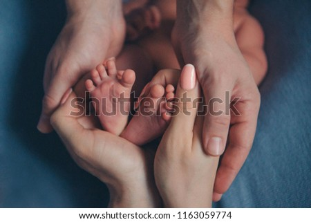 Newborn Baby's feet. Mother and father holding newborn baby legs,legs massage
