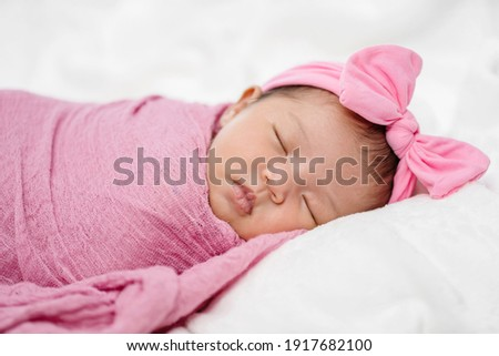 newborn baby sleep in pink cloth wrap blanket on a bed Stock photo ©